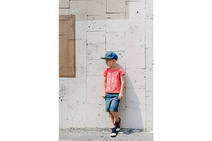 Young happy blond boy leaning on wall, life style kid