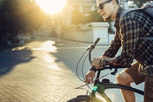Young Man With Backpack And Sunglasses Sits On Bicycle Against Bright Morning Sun