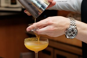 Bartender is pouring cocktail