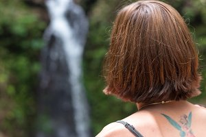 Portrait of young sexy woman in the rainforest of tropical Bali island, Indonesia. Waterfall on a background. Rare view.