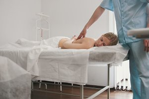 Blonde young woman receiving massage at spa. Relaxation treatment for caucasian model, medicine