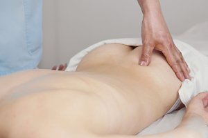 Massage parlor - young girl gets relaxing healing therapy for back