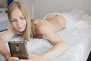The girl lies on a massage table, makes selfie