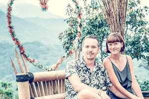 A romantic honeymoon couple on the wooden chair in the mountains of tropical Bali island, Indonesia.