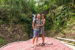 Shot of affectionate young honeymoon couple standing together in rainforest. Couple in love standing near a waterfall in the jungle of tropical Bali island, Indonesia.