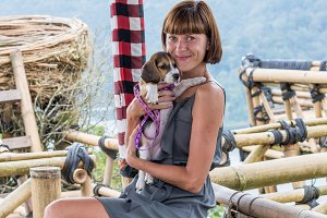 Woman with her beautiful beagle dog in nature of tropical Bali island, Indonesia. Travelling with dog concept.