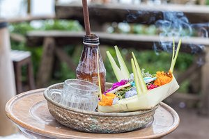 Traditional balinese offerings to gods in Bali with flowers and aromatic sticks. Tropical island Bali, Indonesia.