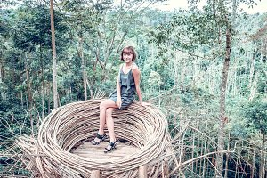 Young woman in artificial nest in rainforest of tropical Bali island, Indonesia.