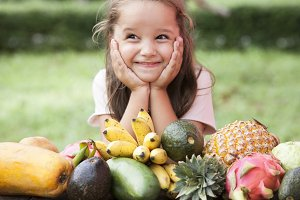 Exotic fruit on wooden table. Summer background with Laughing happy girl