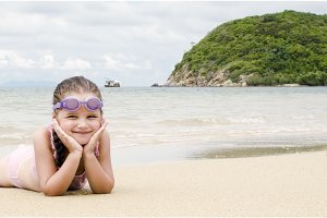 Happy little girl lying on the sand on the beach Female preschooler kid