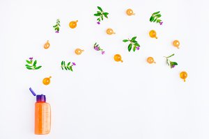 Bottle of essential oil with meadow flowers on white background. Flat lay, top view, natural