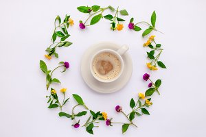 Meadow and wild flowers arranged in circle with coffe cup. Flat lay.