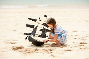 Girl playing on beach flying ship kite. Child enjoying summer.