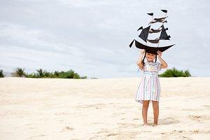Girl playing on beach flying ship kite. Child enjoying summer.