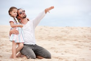 Girl with her happy father in coast ocean. Points to something