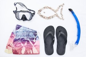 Variety beach accessories for snorkeling on white background. Vacation and travel, sea and ocean items, top view