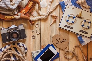 Striped espadrilles, camera and maritime decorations, wooden background