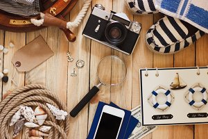 Striped espadrilles, camera and maritime decorations on the wooden background