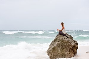 Girl sit at the seaside on the rock and meditating in yoga pose