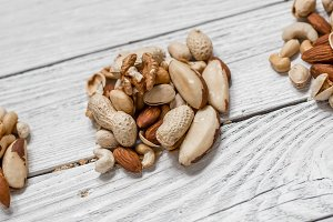different nuts on white wooden background ,