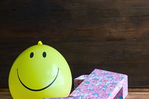 yellow balloon with smile and gift b