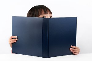Girl peering over the top of a book