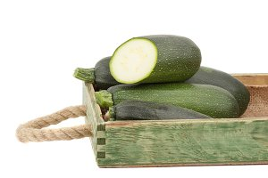 Green fresh zucchini in the wooden tray, isolated