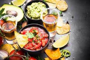 Mexican food party sauce guacamole, salsa, chips and tequila on