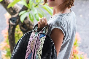 Elegant outfit. Close up of stylish luxury snakeskin python backpack in woman hand. Model holding bag. Female fashion concept.