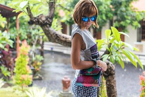 Stylish summer woman holding luxury snakeskin python handbag. Beautiful colors.