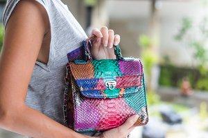Stylish summer woman holding luxury snakeskin python handbag. Beautiful colors. Woman hands with bag.
