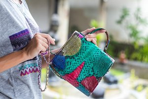 Stylish summer woman holding luxury snakeskin python handbag. Beautiful colors. Woman hands with bag.