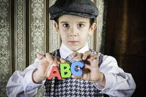 Child in vintage clothes hold letter