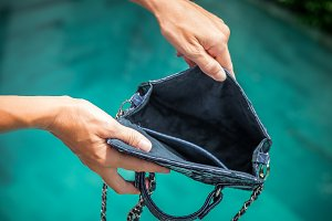 Woman hands opening empty luxury snakeskin python handbag on a swimming pool background