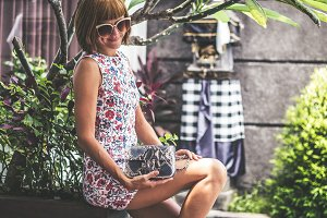 Summer portrait of a beautiful sexy girl with sunglasses and luxury handmade snakeskin python handbag in the swimming pool. Fashion outdoor. Tropical Bali island, Indonesia.
