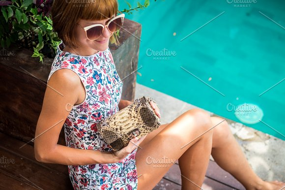 Summer Portrait Of A Beautiful Sexy Girl With Sunglasses And Luxury Handmade Snakeskin Python Handbag In The Swimming Pool Fashion Outdoor Tropical Bali Island Indonesia