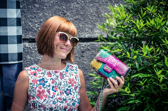 Young Glamour Woman Wearing Flower Dress Posing With Luxury Handmade Snakeskin Python Handbag Beautiful Stylish Girl Holding Handbag And Looking Away Fashion Woman Holding Stylish Bag With Sunglasses
