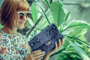 Young glamour woman wearing flower dress posing with luxury handmade snakeskin python handbag. Beautiful stylish girl holding handbag and looking away. Fashion woman holding stylish bag with sunglasses.
