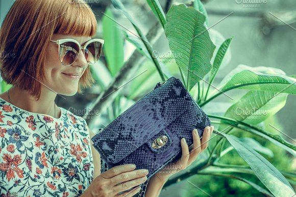 Young Glamour Woman Wearing Flower Dress Posing With Luxury Handmade Snakeskin Python Handbag Beautiful Stylish Girl Holding Handbag And Looking Away Fashion Woman Holding Stylish Bag With Sunglasses