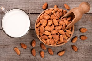 Almond milk in a glass and almonds in a bowl on old wooden background. Top view