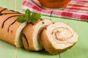 Biscuit swiss roll close-up on green wooden background