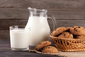 jug and glass of milk with oatmeal cookies in a wicker basket on a wooden background