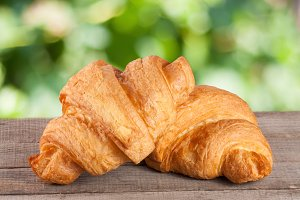 two croissant on a wooden board with a blurry garden background