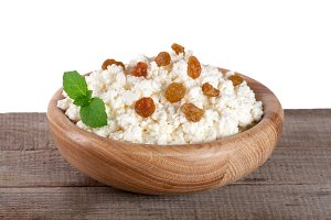 Cottage cheese in a wooden bowl on board with white background