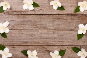 Frame jasmine flowers on the old wooden background with copy space for your text. Top view. Wedding invitation card