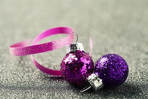 Two bright christmas balls on shiny background