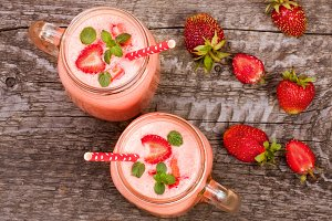 Glass of strawberry yogurt or smoothie with mint leaves on old wooden background. Top view