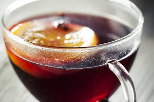 Mulled wine in glass cup with spices on the side