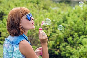 Beautiful young woman blowing bubble in outdoor, nature, near the ocean. Tropical magic island Bali, Indonesia.