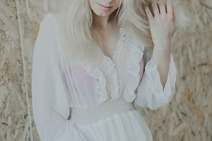 Beautiful stylish blond young woman in a trendy white lace dress
